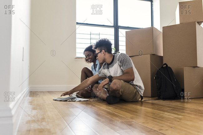 Young couple choosing from color swatches while sitting on floor with boxes at new home
