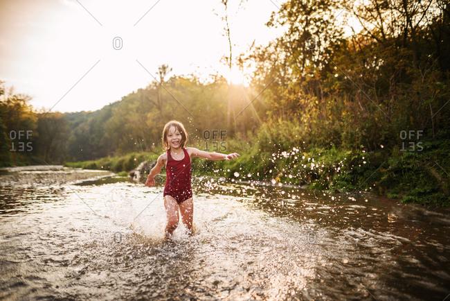 Girl splashing through creek at golden hour
