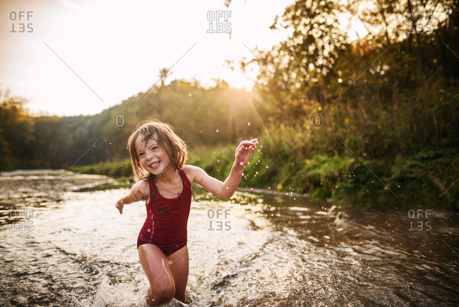 Little girl having fun summer evening playing in the river