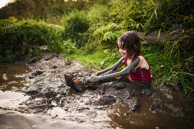 Young girl playing in the mud on river shore