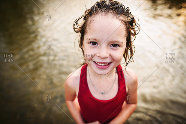 Portrait of happy little girl with wet hair from swimming in the river