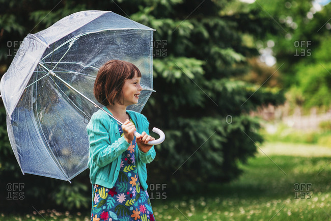 Young girl taking a stroll through the park with an umbrella in the spring