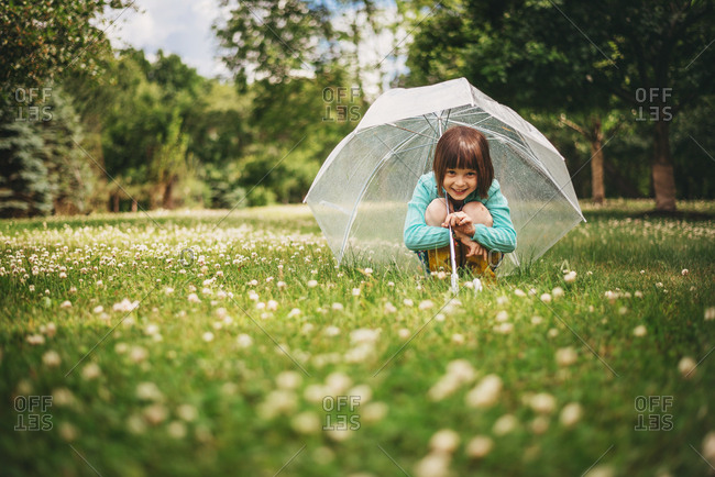 Cute little girl playfully crouching under transparent umbrella in the park