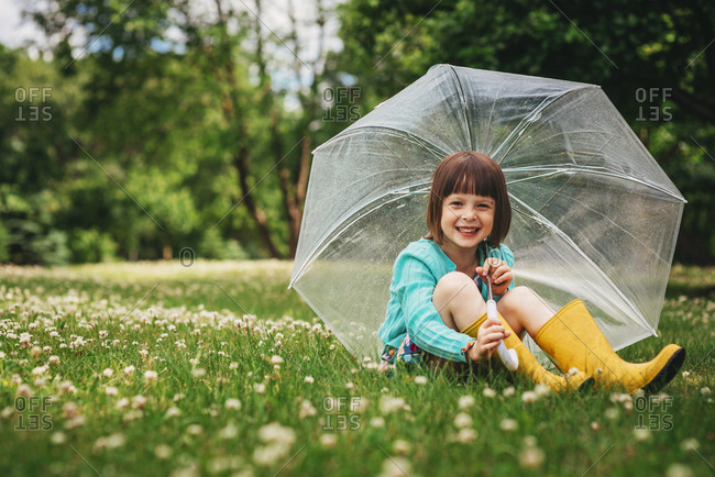 Spring portrait of little girl with rain boots and umbrella