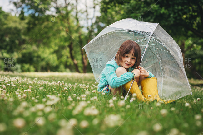 Young girl relaxing with umbrella in lush field of wildflowers