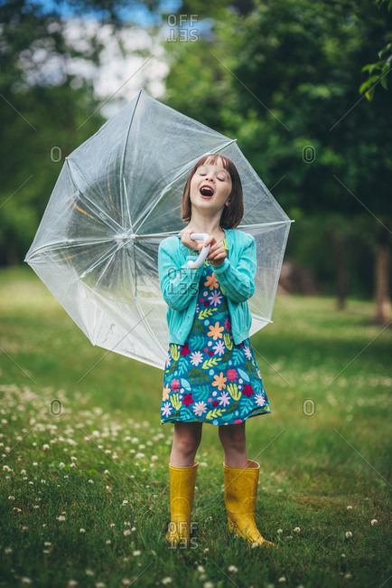 Little girl making expressive face holding umbrella behind her standing in the park