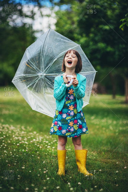 Young brunette girl posing with umbrella in vibrant spring children's fashion