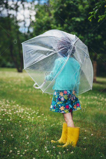 Back view of little girl in spring outfit turned away with clear umbrella