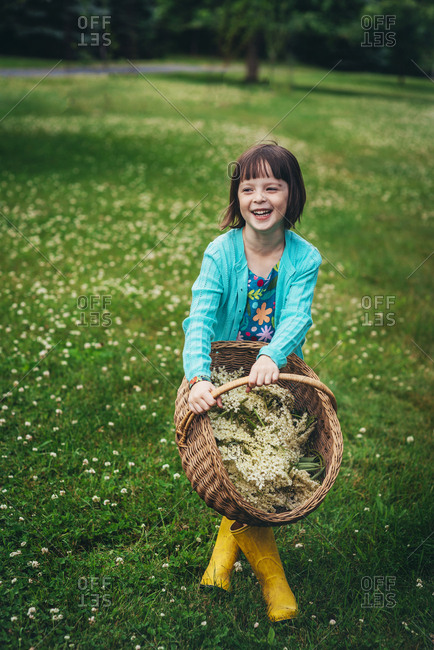 Young girl standing with legs crossed in backyard and laughing with basket of elderflowers