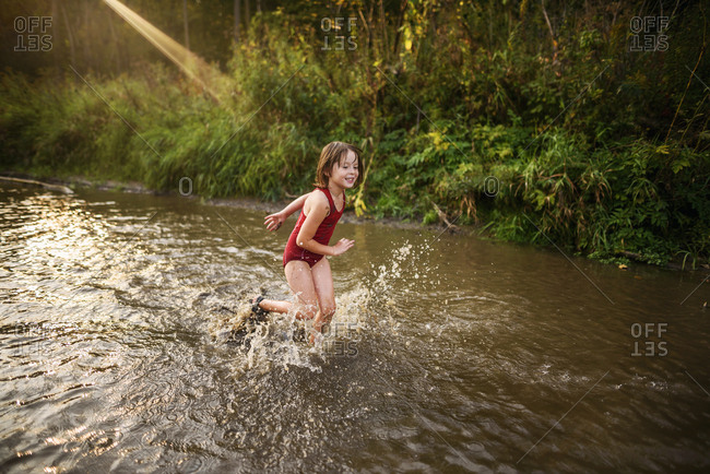 Young girl playing in a river on a summer evening