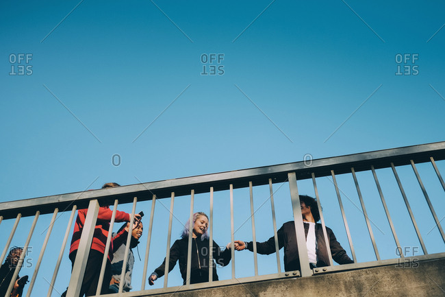 Smiling friends while walking below bridge