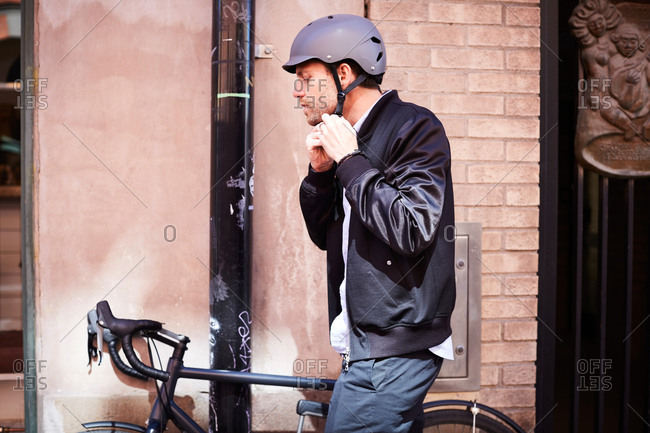 Side view of businessman wearing helmet while sitting on bicycle by wall at city