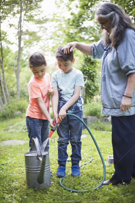 Grandmother looking at grandsons filling watering cans from garden hose in back yard