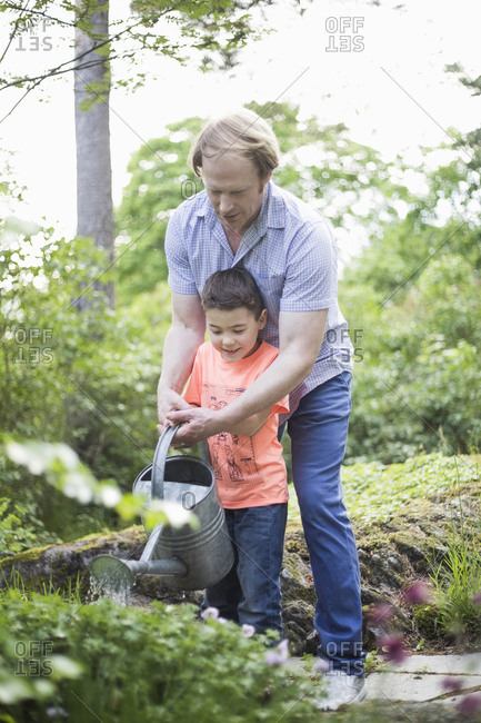 Father and son watering plants with can in back yard