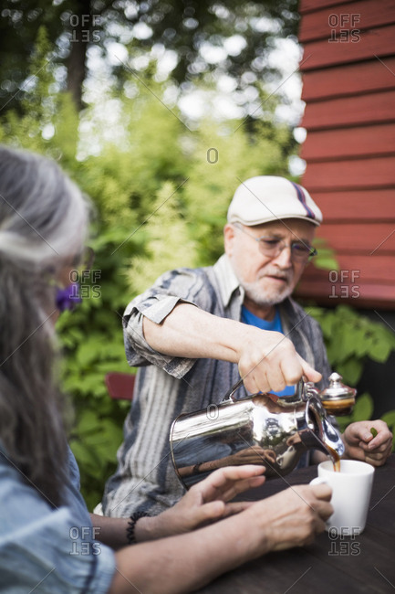 Senior man pouring coffee in cup for woman at back yard