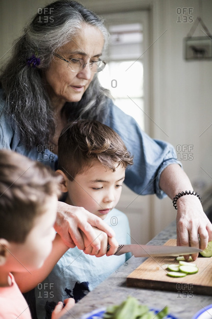 Grandmother assisting grandson cutting cucumber in kitchen at home