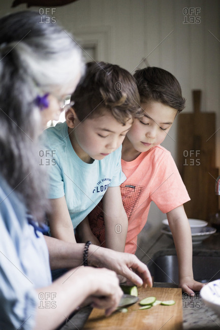 Grandsons looking while grandmother cutting cucumber on board in kitchen at home