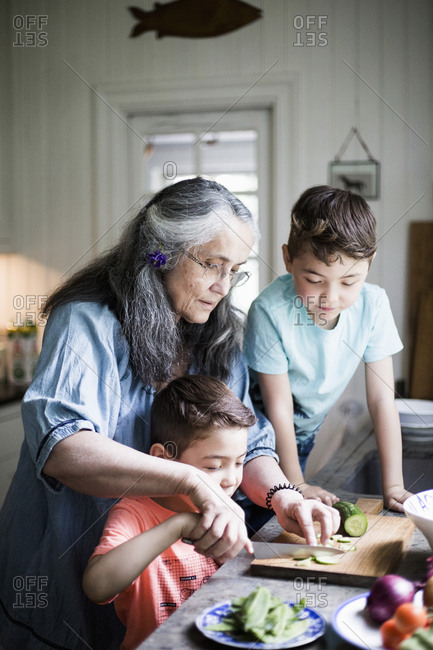 Grandmother assisting boy cutting cucumber on board in kitchen at home