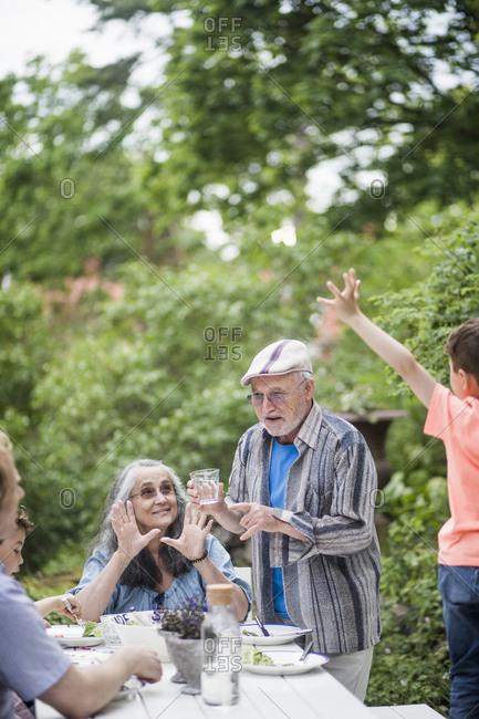 Multi-generational family enjoying lunch in back yard