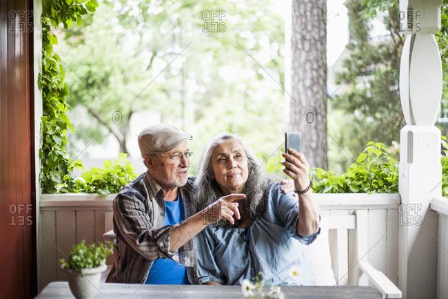 Senior couple taking selfie in porch