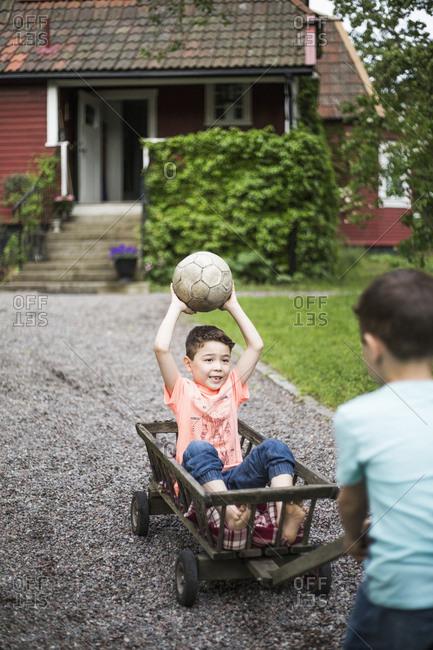 Twin boys playing on footpath in back yard
