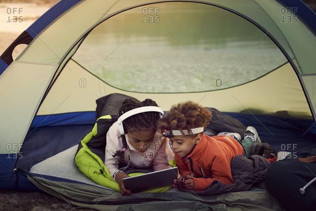 Siblings with digital tablet lying in tent