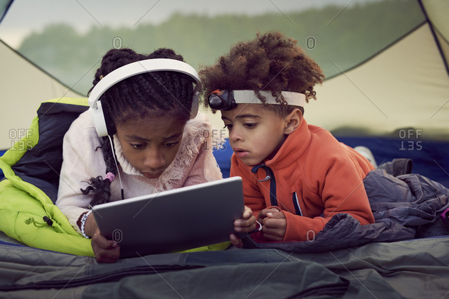 Brother and sister lying in tent while using digital tablet
