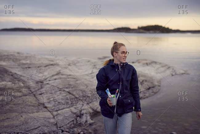 Young woman walking with toothbrush and toothpaste in container at beach during sunset