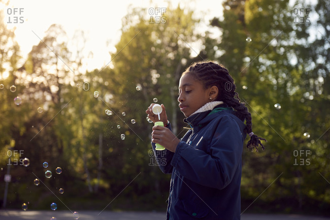 Side view of girl holding bubble wand against trees at campsite