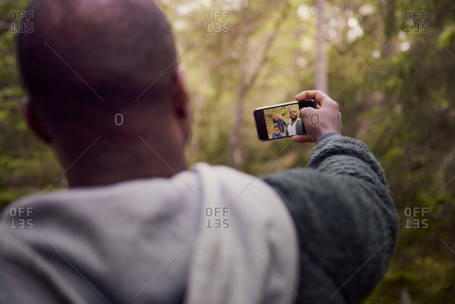 Man taking selfie with family in forest