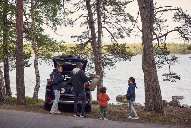Family unloading car trunk on roadside during camping at beach