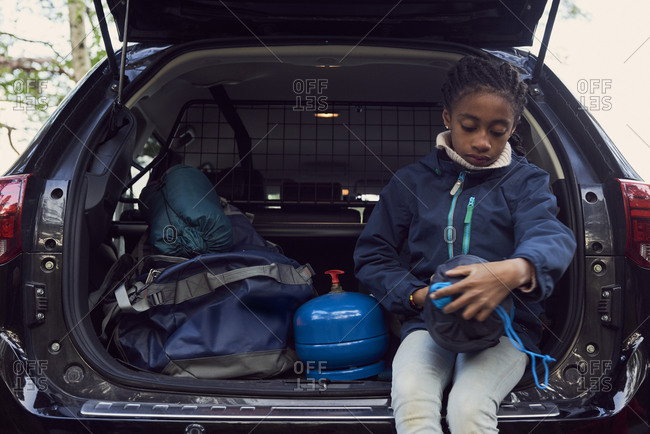 Girl sitting with camping gear in car trunk