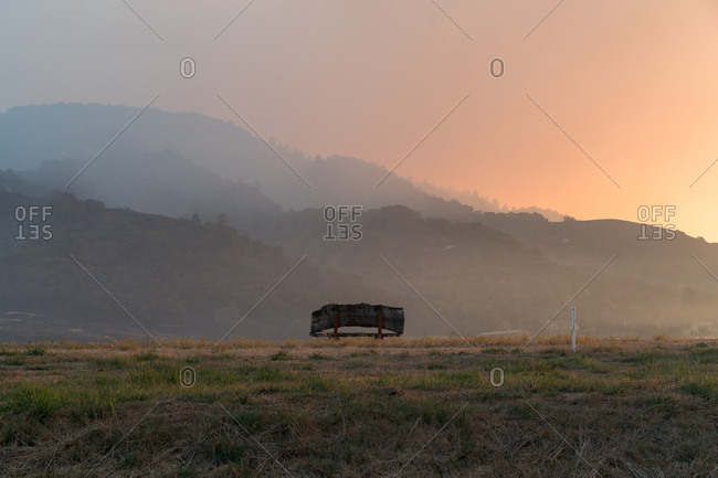 Lonely bench in smoke filled valley with glow of wildfires on horizon