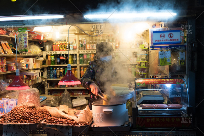 Beijing, China - December 13, 2017: Food seller picking corn on the cob out of boiling water in a stall