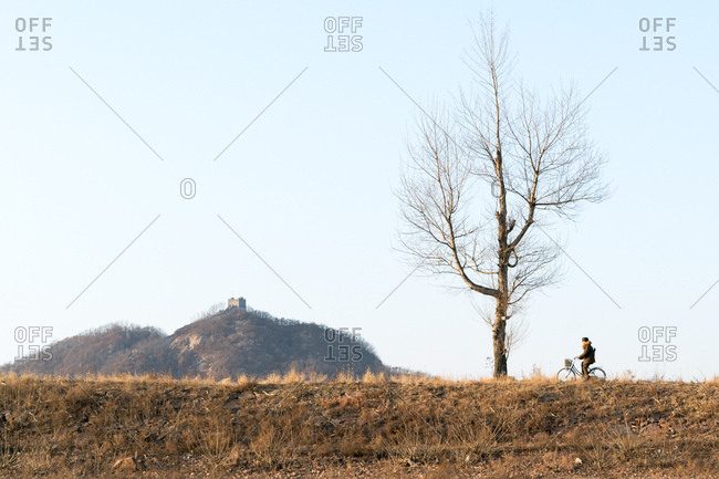 North Korean border guard riding bicycle on opposite riverbank