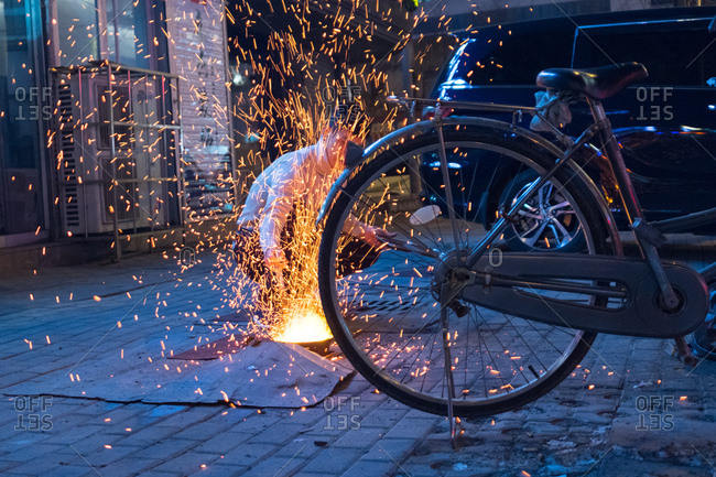 Dandong, China - December 18, 2017: Sparks from coals engulf a worker outside a Korean barbecue restaurant