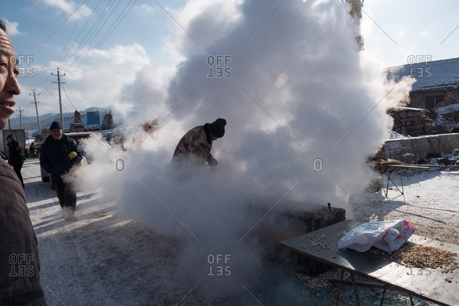 Changbai, China - December 19, 2017: Steam escapes from a popcorn vendors pressure cooker in freezing temperatures at a street market