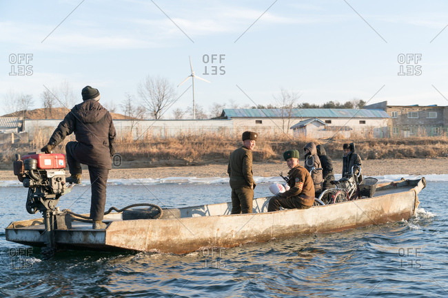 Sinuiju, China - December 25, 2017: North Korean border guards and other passengers cross river on small boat
