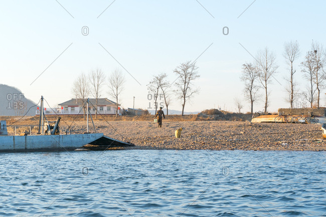 North Korean border guard climbing riverbank after disembarking from a boat in Sinuiju, North Korea