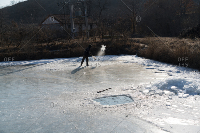 Man clears ice off frozen pond after chopping fishing hole with axe in Northeast China