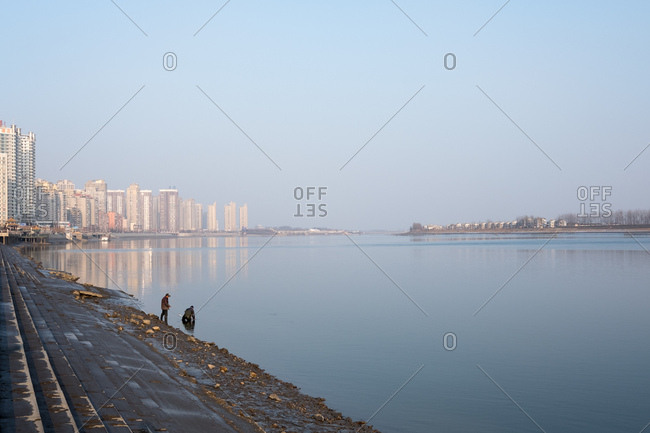 Tower blocks dominate the Chinese side of the Yalu river in contrast to the small settlement on the North Korean side