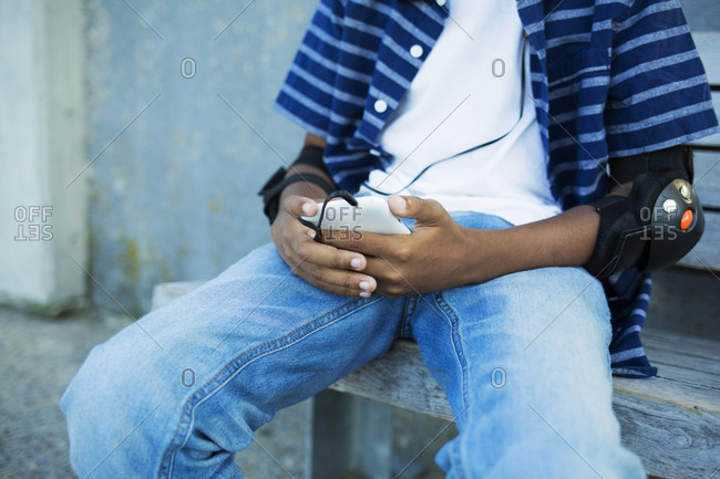 Midsection of boy wearing elbow pads holding smart phone while sitting on bench