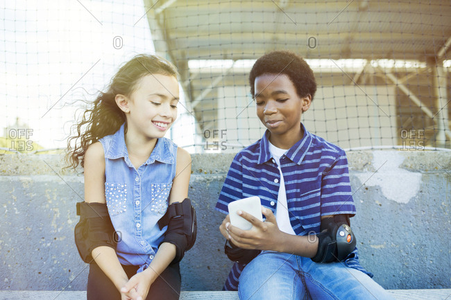 Boy showing mobile phone to smiling friend while sitting on park bench