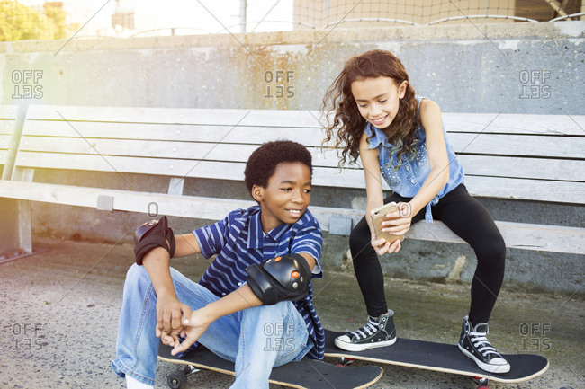 Boy and girl looking at mobile phone while sitting with skateboards on park bench
