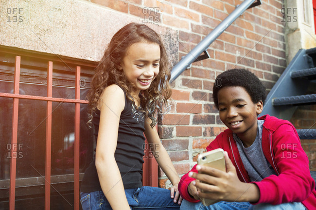 Smiling boy showing smart phone to female friend while sitting on steps in city