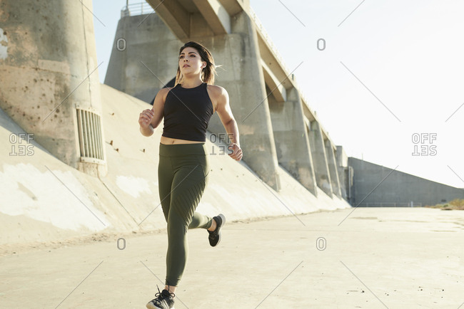Determined young woman jogging on road