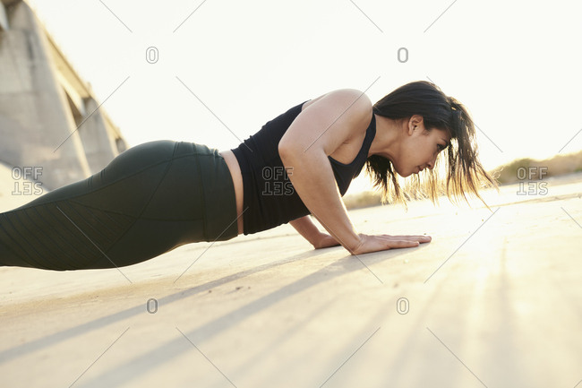 Dedicated woman doing pushups on footpath against sky during sunny day