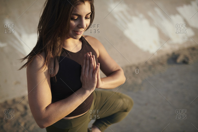 High angle view of smiling young woman meditating