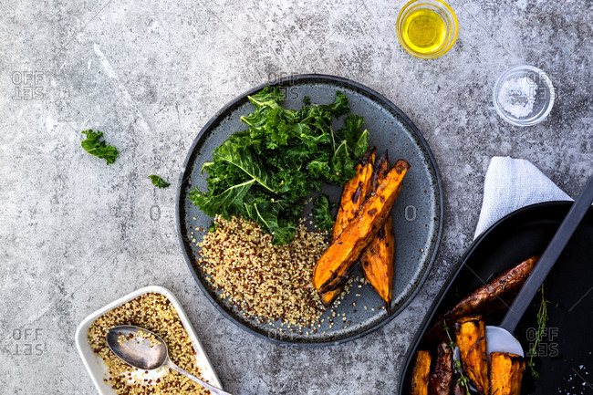 Kale, quinoa and roast sweet potato wedges served on plate as part of vegan bowl