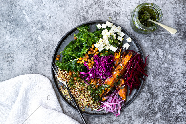 Vegetarian bowl consisting of kale, quinoa, roast sweet potato wedges, red cabbage, beetroot, chickpeas and feta cheese